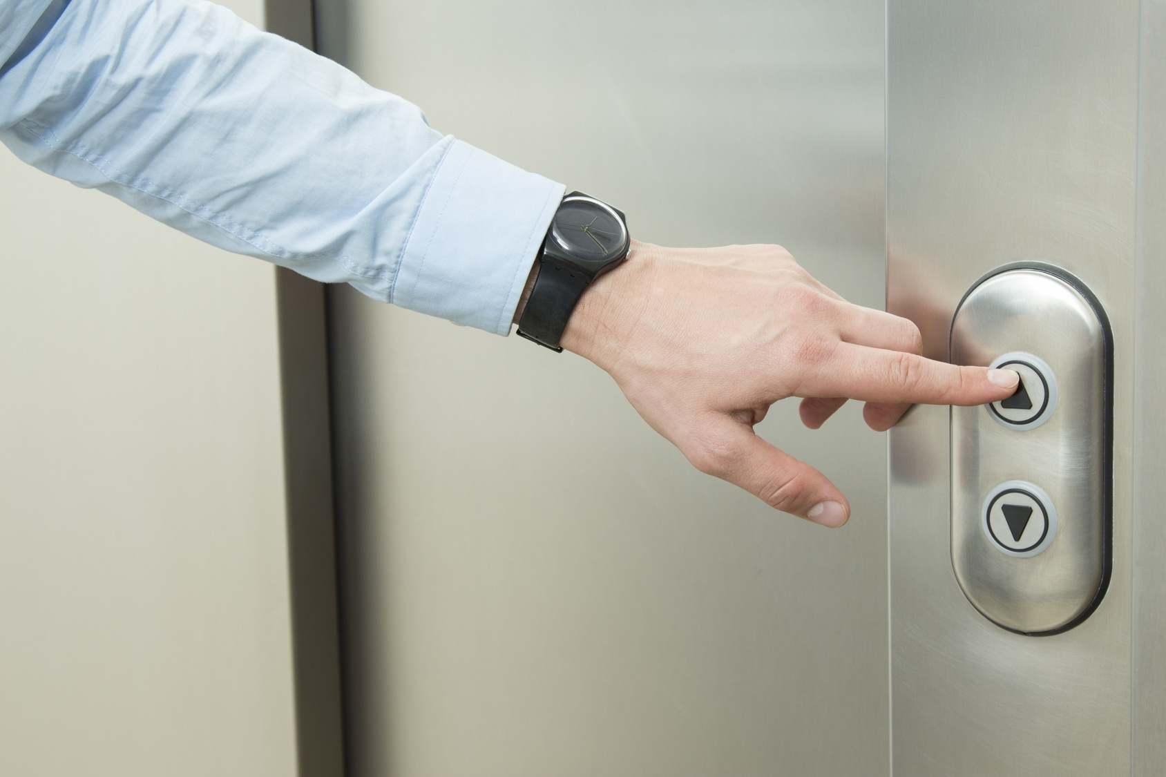 "Man pushing ""Up"" button to call elevator"