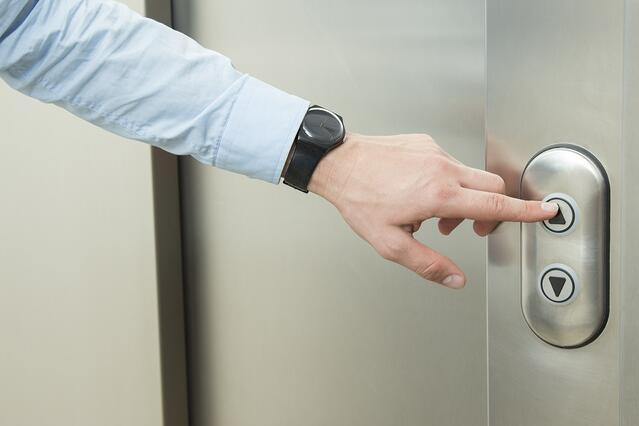 """Man pushing """"Up"""" button to call elevator"""